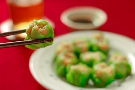 chinese menu: Close up using chopsticks hold Chinese dumpling. Chinese food Dim sum concept with red background.