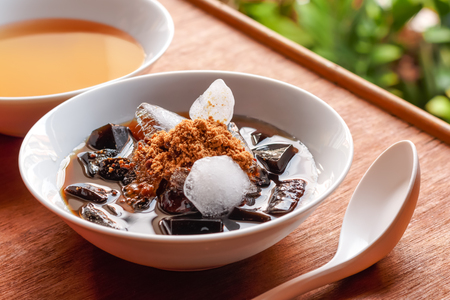 gelatin: grass jelly dessert  herbal gelatin , syrup, ice, and brown sugar on the wooden background. Chinese style.