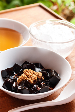 grass jelly dessert  herbal gelatin , syrup, ice, and brown sugar on the wooden background. Chinese style. Zdjęcie Seryjne - 46534647