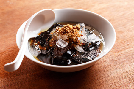 grass jelly dessert  herbal gelatin , syrup, ice, and brown sugar on the wooden background. Chinese style. Stock Photo - 46534654