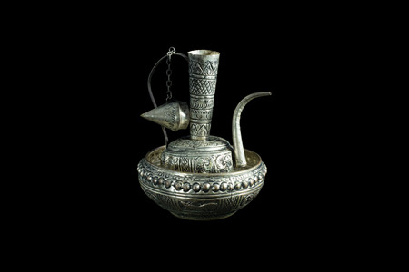 Old silver ewer container pour water, Buddhism on black background.
