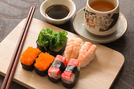 wiki: Sushi set with chop sticks and soy sauce served on wooden slate - Sushi is a food originating in Japan, consisting of cooked vinegar rice combined with other ingredients such as seafood, vegetables