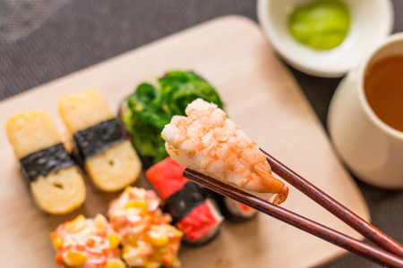 Sushi set with chop sticks, wasabi served on wooden slate, selective focus - Sushi is food originating in Japan, consisting of cooked vinegar rice combined with other ingredients such as vegetables