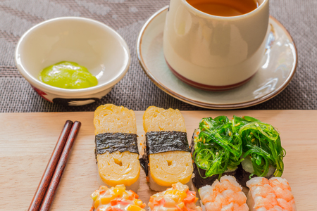 wiki: Sushi set with chop sticks, wasabi served on wooden slate, selective focus - Sushi is food originating in Japan, consisting of cooked vinegar rice combined with other ingredients such as vegetables