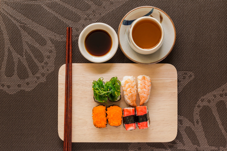 chop sticks: Sushi set with chop sticks and soy sauce served on wooden slate - Sushi is a food originating in Japan, consisting of cooked vinegar rice combined with other ingredients such as seafood, vegetables