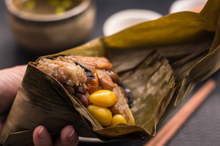 Freshly cooked Zongzi wrapped with bamboo leaf holding and peeling on woman hands with dark background. Zongzi is a traditional Chinese food eaten during the dragon boat festival. Stock Photo