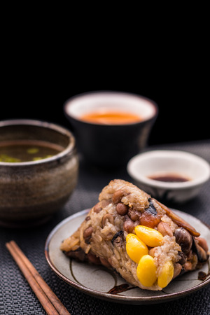pronunciation: Zongzi or Asian Chinese sticky rice dumplings with Yellow tea, soup, sauce and chopsticks on dark table surface. Zongzi is a traditional Chinese food eaten during the dragon boat festival. Stock Photo