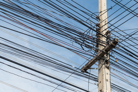 disorganized: Electric pole and disorganized, messy electricity line with against blue cloudy sky, abstract background.