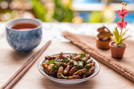 Fried insects - Wood worm insect crispy with pandan after fried and add a light coating of sauce and garnish Thai pepper powder with chopsticks, tea, brown cloth on wooden background, Select focus Stock Photo