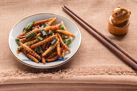 Fried insects - Wood worm insect crispy with pandan after fried and add a light coating of sauce and garnish Thai pepper powder and chopsticks on brown cloth background, select focus