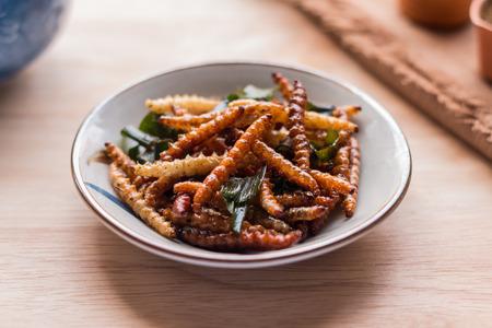 gusanos: insectos fritos - gusano de bambú crujiente de insectos con pandan después de frito y añadir una ligera capa de salsa y aderezo de pimienta tailandesa en polvo en el fondo de madera. insectos fritos son el alimento de bocado popular en Tailandia