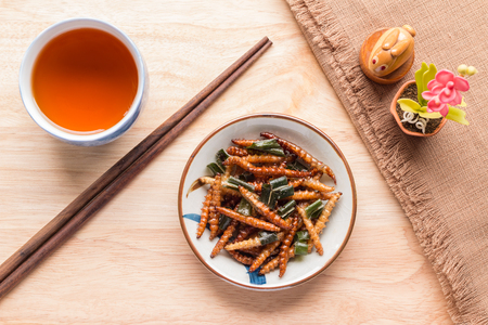 Fried insects - Wood worm insect crispy with pandan after fried and add a light coating of sauce and garnish Thai pepper powder with chopsticks, tea, brown cloth on wooden background, Top view
