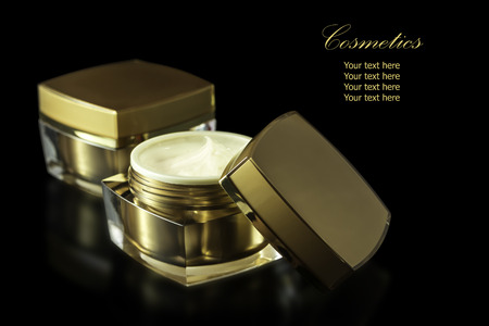 reflexion: El oro de color blanco para el envase cosmético humectante crema para la cara aislada en el fondo negro con la reflexión. El archivo incluye un trazado de recorte por lo que es fácil de trabajar. Foto de archivo