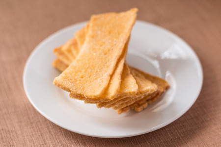 Sliced crispy bread in white ceramic dish on brown tablecloth background.