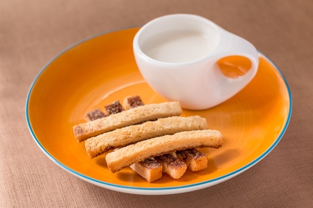 nicely: Sliced crispy bread in orange ceramic dish with glass of milk on brown tablecloth  background.