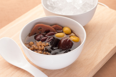 Cold assorted beans in syrup Chinese traditional. Kind of Chinese dessert. Sugar peas a dessert of China. There is a combination of several green, lotus, persimmon, jelly, millet, boiled with sugar. Stock Photo