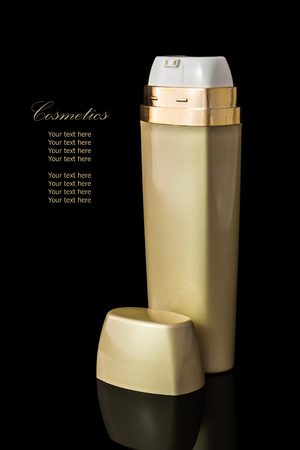 reflexion: Gold colored blank cosmetic container for face cream moisturizer isolated on black background with reflexion.