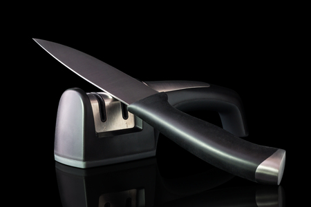 sharpening process: Knife to fillet and two way hand held knife sharpener with reflexion for products isolated on black background.
