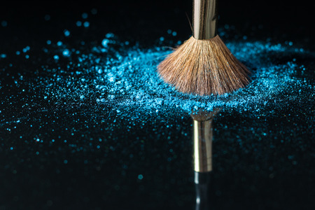 feminine beauty: Makeup brush on professional cosmetic on background with colorful powder. Makeup background. Stock Photo