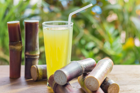 Sugarcane fresh juice with piece of sugarcane on wooden background. Closeup image / Selective focus