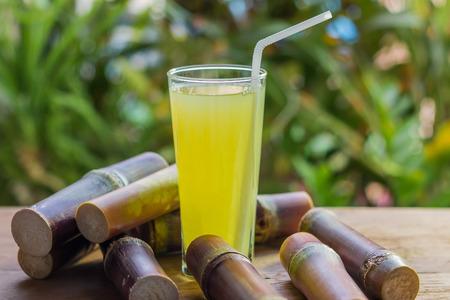 molasses: Sugarcane fresh juice with piece of sugarcane on wooden background Stock Photo