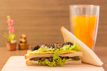 Sandwich made of fried insect meat and mozzarella cheese, mayonnaise and tomato, lettuce with orange juice presented on a wooden board. Close-up, Select focus.