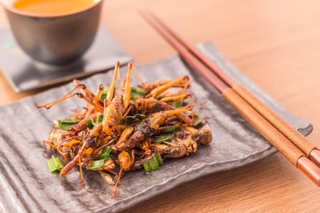 Fried insects - Wood worm insect crispy with pandan after fried and add a light coating of sauce and garnish Thai pepper powder with chopsticks, tea, on wooden background