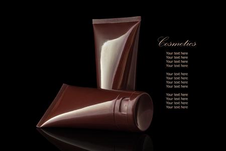 reflexion: Marrón de color blanco para el envase cosmético humectante crema para la cara aislada en el fondo negro con la reflexión. El archivo incluye un trazado de recorte por lo que es fácil de trabajar.