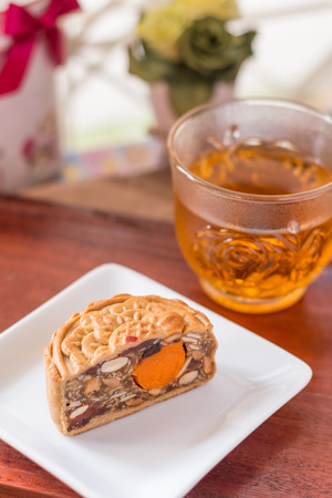 Moon cake and tea - Chinese traditional moon cakes on white plate and table setting with teacup. Closeup, Select focus. Stock Photo