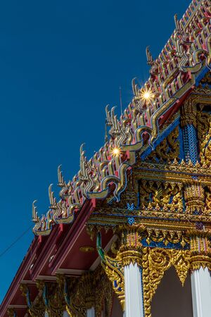 Temple roof vintage Thai style with against blue sky background - Art architecture Temple roof of Wat Phutthabucha in Thung Khru, Bangkok, Thailand. Side view. Stock Photo