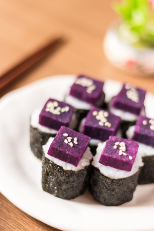 kitchen island: Sushi - Purple sweet potato in sushi rice with white ceramic plate. The benefits of purple sweet potato are high Beta Carotene and Carbohydrate used in cooking. Close up