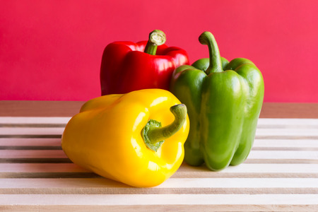 Peppers - Yellow, Green and red peppers on white wooden board with red background. Pepper is vegetable that can be used to cooking. Close up Stock Photo