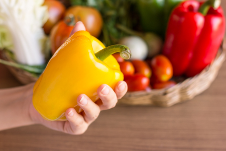 Peppers - Yellow peppers in woman hand with group of peppers background. Pepper is vegetable that can be used to cooking. Close up