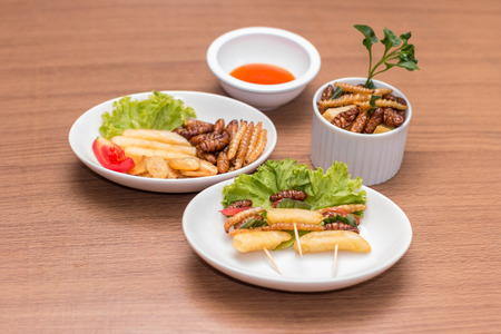Insects - Wood worm, Silkworms fried insect, Tasty potatoes fries and chopsticks on white plate with wooden background.  Insects is preferable for the people of Cambodia and Thailand. Select Focus