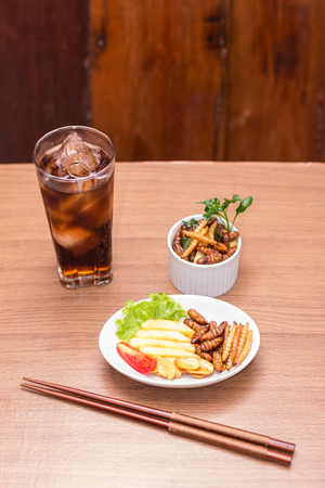 preferable: Insects - Wood worm, Silkworms fried insect, Tasty potatoes fries and chopsticks on white plate with wooden background.  Insects is preferable for the people of Cambodia and Thailand. Select Focus