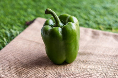 Peppers - Green bell pepper on burlap hessian sacking with grass background. Pepper is vegetable that can be used to cooking. Close up Stock Photo
