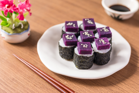 Sushi - Purple sweet potato in sushi rice with white ceramic plate. The benefits of purple sweet potato are high Beta Carotene and Carbohydrate used in cooking. Close up