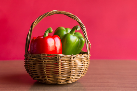 Peppers - Red and Green peppers in the vintage basket on wooden table with red background. Close up