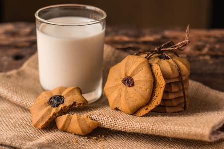 Chocolate chip cookies and a glass of milk on a on the hessian napkin background. Vintage, Closeup.