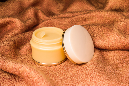 Cosmetics containers - Open blank cap white color cosmetic, Moisturizer containers for various makeup products on light brown cloth background, ready for your design product.