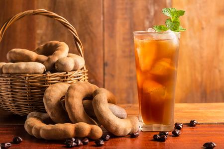 타마 린드 주스 - 맛있는 달콤한 음료 타 마 린드와 박하와 함께 소박한 나무 테이블에 나뭇잎. 선택적 포커스 및 톤된 이미지입니다. 공간을 복사합니 스톡 콘텐츠