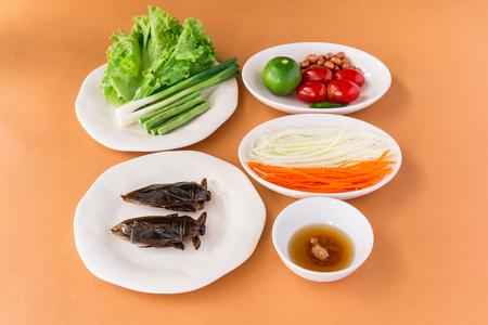 Papaya Salad - Lethocerus indicus (Giant water bug) and Green Papaya Salad with long-beans, roasted peanuts, tomatoes, lemon, raw papaya, carrot, dressing (palm sugar) and lettuce. Traditional spicy Thai food.