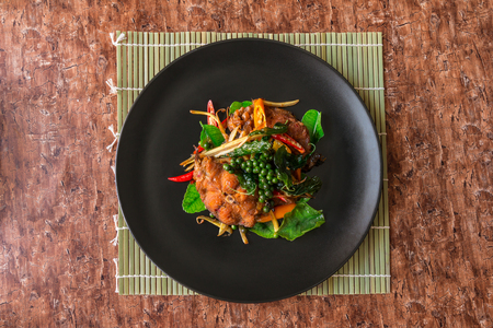 Spicy Catfish - Spicy catfish with spices, black pepper, red chilli, kaffir lime leaves and stir-fried crispy catfish served in black plate on wooden table. Thai spicy herb food. Traditional.