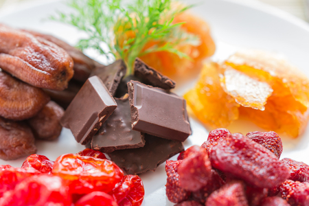 Mixed dried fruits with chocolate in round shape, dried tomatoes, pineapple preserves, strawberries, preserved mango sheet and dried banana, health food concept, Closeup