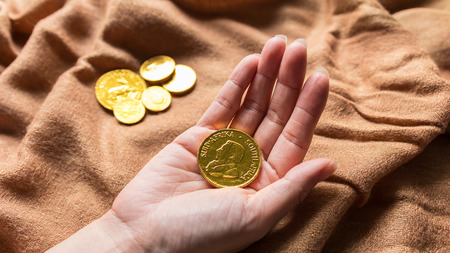 Chocolate money, Chocolate gold coins in woman hands as a concept for finance. Horizontal, Closeup, Select focus.  Foto de archivo