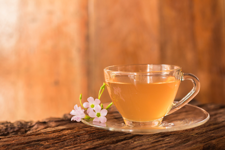Ginger teacup and pink flower on a wooden table background, Beverage concept, Close up, Selective Focus.