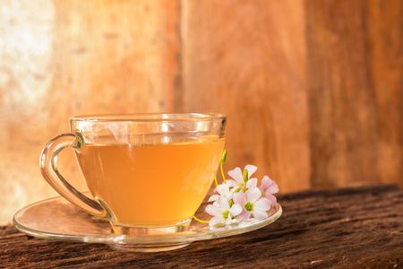 Ginger teacup with ginger slices and pink flower on a rostic wooden background, Beverage concept, Close up, Selective Focus.