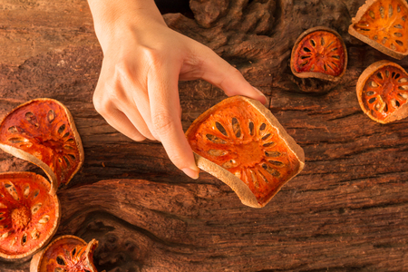 Dried Bael fruit organic herb for Skin, Hair, and Health in girls hands on a rustic wooden background