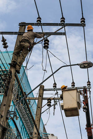 Bangkok, Thailand - August 5, 2017: Electrician working on electric pole at an altitude to installs cable high voltage against to transformer with cloudy sky.  Stock Photo - 98389962