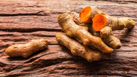 Turmeric root - Fresh turmeric root and sliced on the old plank with nature background. Close-up, Selective focus.